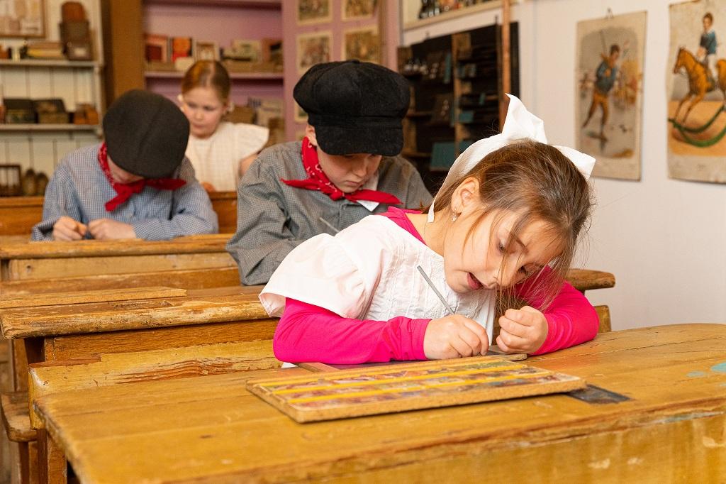 Het meisje in Ot en Sien kleding, met een witte strik in het het lange haar, zit in het oude houten schoolbankje heel geconcentreerd met een griffel op een lei te schrijven.